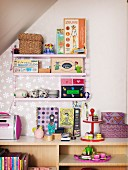 Pink String shelves holding doll's tea set and various toys above open-fronted shelving unit