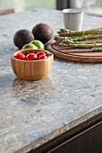 Wooden bowl and chopping board with vegetables on stone worksurface