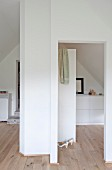 White installations and pale wooden floor in attic bedroom with ensuite bathroom
