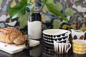 Bread on wooden board next to breakfast crockery with retro patterns