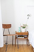 Wooden chair with metal frame next to small, wooden, fifties-style side table