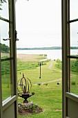Blick durch offene Terrassentüren auf Wiese und den angrenzenden See