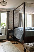 Canopy bed with dark wooden frame in rustic bedroom