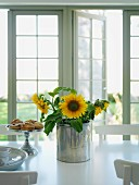 Sunflowers in metal container next to pastries on cake stand on white table