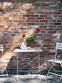 White garden table and chairs against brick façade