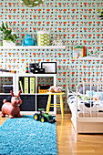 Blue flokati rug in front of half-height shelving and bed with white metal frame against wall with patterned, children's wallpaper