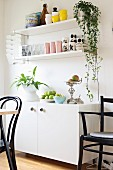 Fruit bowls and houseplants on white sideboard below white shelves on wall in dining room with black chairs