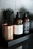 Copper-coloured metal beaker and soap dispenser on black shelf