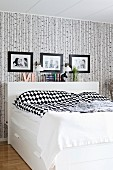 White box-spring bed with headboard and black and white patterned bed linen below framed family photos on patterned wallpaper