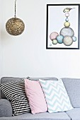 Patterned scatter cushions arranged on grey sofa below pendant lamp with spherical metal lampshade