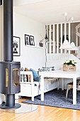 White table and bench under two pendant lamps next to black, cast iron log burner