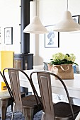 Retro metal chairs at white dining table below pendant lamps with ceramic lampshades