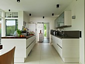 Two facing counters in open-plan kitchen with large floor tiles and doorway leading to foyer in background