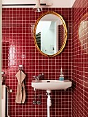Sink below oval gilt-framed mirror on red-tiled wall in corner of modern bathroom