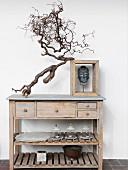 Schlichter Holztisch mit Schubladen und Ablagen, obenauf abgeschnittener Ast neben Buddhakopf im Holzrahmen
