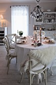 Festively set table in candlelight below chandelier with glass ornaments in shabby-chic dining room