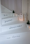 White-painted winding staircase with motto painted on risers and various vintage-style candle lanterns on treads