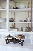 Old kitchen scales and white crockery in shabby-chic dresser with glass-fronted top section