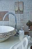 Modern tap fitting and painted basin on washstand in front of pale brown wall tiles
