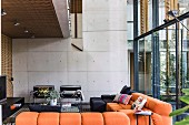 Modern lounge with orange upholstered sofa under gallery, in the background exposed concrete wall in contemporary architecture