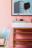 Black-framed picture above open shelves in retro interior with pastel pink wall
