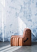 Brown leather modular armchair against wall