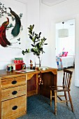 Vintage desk, wooden chair, wooden toys, white-framed picture of birds and view into child's bedroom