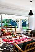Comfortable lounge with 50s couches and armchair, colourful modern rug and unobstructed view of garden