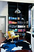 Books sorted by colour on black fitted bookcase, cow-hide rug and mustard-yellow armchair in elegant period apartment