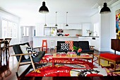 Retro lounge with colourful rug and exotic-wood parquet floor in open-plan interior with view of white kitchen