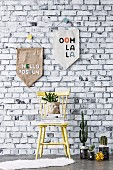 Homemade pennants in front of wallpaper with a brick wall motif, in front of a wooden chair and cacti