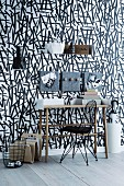 Console table, felt-covered pinboards and metal shelf on wall with black and white wallpaper