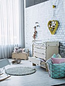 Baby-changing cabinet and wire basket of cushions below heart-shaped yellow shelving unit hung on wall