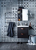 Towel rail and sink with black base unit below mirrored cabinet hung on wall with black and white tile-patterned wallpaper