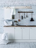 White base units, washing-up brushes hung from hooks and clothes airer suspended from ceiling in utility room with brick-patterned wallpaper