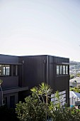 Charcoal-grey metal façade of modern, cubist house with view over Brisbane, Australia