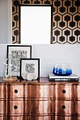 Coral under glass cover, framed black and white wallpaper patterns and blue glass bowl on copper chest of drawers below mirror reflecting wallpaper with geometric pattern