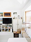 Crammed, open-fronted shelves, TV and framed family photos in comfortable lounge area