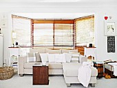 Comfortable sofa with scatter cushions in front of vintage side tables in bay window