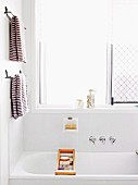 Bathtub with toiletries in wooden bath caddy below brown and white stripes towels on towel rails