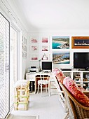 Gallery of photos above monitor on vintage desk and stool next to terrace doors