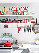 Collection of tins on kitchen shelf and magnetic knife rack in simple, retro-style kitchen