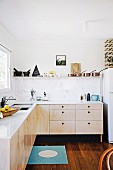 Modern, minimalist kitchen with wooden fronts and white worksurface