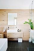 Designerbad mit Holzverkleidung, Glasabtrennung und schwarzem Fliesenboden
