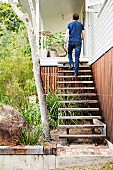 Man walking up rustic wooden steps without handrail into house entrance from green front garden planted with grasses and bushes