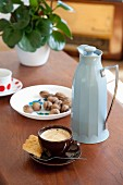 Cup of espresso and pale blue thermos jug