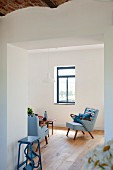 Renovated foyer with open doorway and view of fifties-style armchair with pale blue cover in minimalist interior