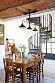 Dining area in front of cast-iron, vintage-style spiral staircase in open-plan interior