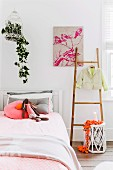 Bright, girl's bedroom with orange and pink accents and house plant in vintage birdcage