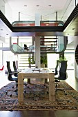 Futurist interior with study area in luxury apartment; rustic wooden table and Eames office chairs in foreround